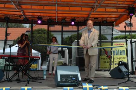 Ambassadör Dag Hartelius klipper det blågula bandet vär att visa  att Sverigedagen är invigd.