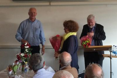 Kent Larsson delar ut blommor – till Magda Stoltz, som till övriga gästers förtjusning spelade under hela festen, och till jubileumsföreläsaren Kjell Albin Abrahamson. Foto: Gunilla Lindberg.