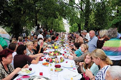 Shabbat Shalom – med tända sabbatsljus, välsignat vin och en uppsjö av traditionella judiska maträtter. Besökarna slår sig ner vid långbordet på Grzybowskitorget för att inviga sabbaten. Foto: Stanisław Godula