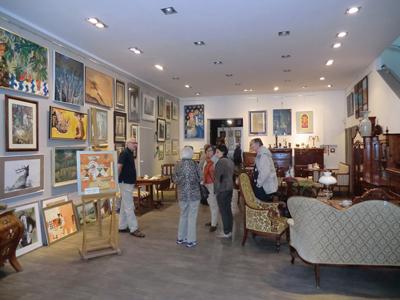 Galleriinnehavaren Ryszard Lyczak guidar en grupp besökare genom samlingarna.