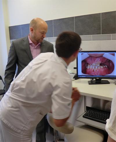 Tandläkaren visar röntgenbilden och diskuterar åtgärderna med patienten.  Foto: Gunilla Lindberg.