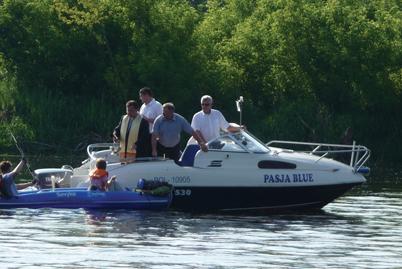 Prästen stänker välsignat vatten över båtar och kanoter.