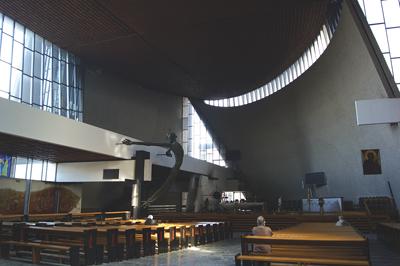 Spänd som en pilbåge, rakt ut i kyrkorummet, hänger Kristusgestalten, skapad av skulptören Bronisław Chromy.