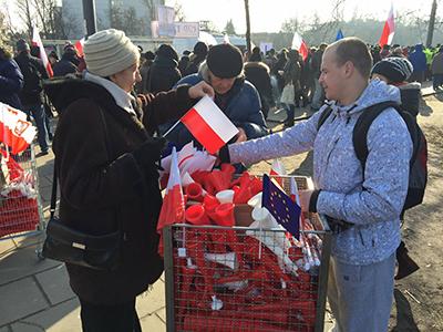 Röd-vita flaggor och tutor delades ut av KOD. Foto: Ted Bergdahl.