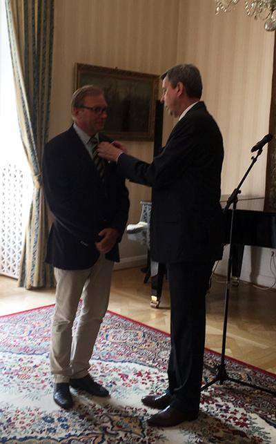 Maciej Onoszko får hederstecknet fäst på kavajslaget av ambassadör Wiesław Tarka.