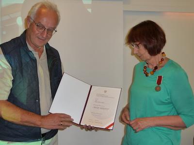 Kent Larsson överlämnar medaljen Bene Merito till Gunilla Lindbegr. Foto: Ela Lovén.