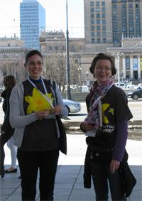 Två frivilliga delar ut sina sista papperspåskliljor vid metrostation Centrum intill Kulturpalatset söndag eftermiddag.